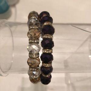 Jewelry - Gold and purple elastic band bracelets.